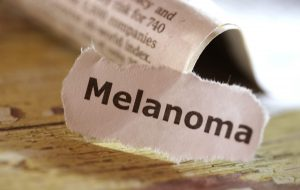 Word Melanoma cut out from a newspaper