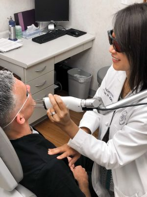Dr. Karen Kim treating a male patient's melasma with a laser device