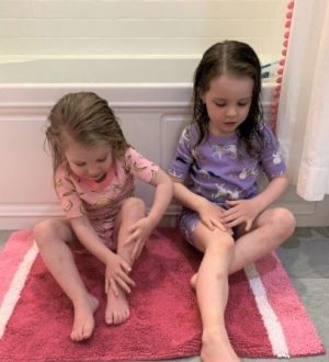 Young sisters lathering moisturizer on their legs after bathing
